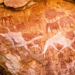 Ennedi plateau. Wall of shallow sandstone cave. Bichrome images of cattle with white udders and person with round head, facing forward and flanked by two small figures, are all superimposed by white camel running to right. Horse and Camel Periods. Image ID: chaenp0020022