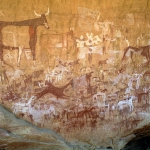 Ennedi Plateau. Huge panel of mainly bichrome paintings on rear wall of cave. Top left, large bichrome cow with udder facing right superimposing outline white cow facing left. Bichrome man stands behind large cow holding arrow(?). Numerous cattle, woman in skirt, running red camel, goats and sheep surround big cow. To right of cow, white geometric shapes are remains of bichrome cattle. Below, red and white horses with horsemen holding swords. Numerous small people facing forwards. Image ID: chaenp0050021