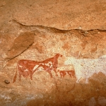 Tassili du Kozen. From left, bichrome red and white man wearing clock and headdress and holding white stick faces towards bichrome elongated cow with udder facing right, bichrome calf, and silhouette white bull facing left. Image ID: chatdk0010051