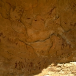 Wadi Sura. Large panel of bichrome maroon and white(?), and faded paintings in main cave. Numerous male figures painted in maroon and probably white (now faded), negative handprints. Round Head Period. Image ID: egywsu0010006
