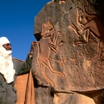 "Messak. Tuareg guide standing beside so-called panel of ""fighting cats"". Image ID: libmes0040128"