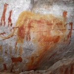 Yellow painting of a large elephant overlays red paintings of animals and human figures. In the middle ground several animals are depicted on a rope or string, SOASWC0060002