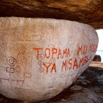 Lake Victoria, Uganda. Graffiti written in Kiswahili, in modern oil-based paint, covers some of the original geometric symbols. Translated the graffiti means: 'do not defecate in the Devil's house'. Image ID: ugavic0060003