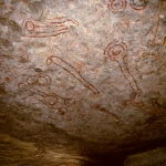 Lake Victoria, Uganda. Paintings in red and originally in-filled in white cover the underside of a boulder forming the roof to a shelter. The art is attributed to Twa peoples. The age of the paintings is uncertain. Image ID: ugavic0060005
