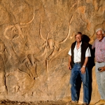 Djanet, Algeria. Trust for African Rock Art's recording team, David Coulson (left) and Alec Campbell standing standing next to cattle engravings. Image ID: algdja0060010