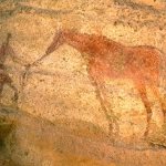 Tarssed Jebest, Algeria. Faded red standing man holding reins of faded red horse facing left. Image ID: algtdj0010016