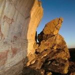 Tsodilo Hills. Finger paintings in red of eland and giraffe, and positive handprints, with setting sun lighting right-hand side. Image ID: bottsd0040004