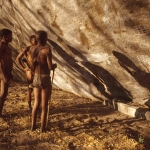 Tsodilo Hills. Three Zhu Bushmen examine white paintings in White Paintings Shelter. Image ID: bottsd0520001