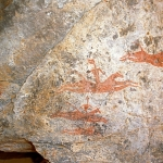 Archei Guelta. Outside cave on exposed sandstone cliff. Four red horses, two with armed riders, gallop right. At left, horizontal human figure flies after horses. Horse Period. Image ID: chaarg0020004