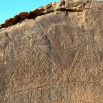 Ennedi plateau. Details of two large decorated figures. Note square hole in rock base below feet of figures. Image ID: chaenp0010030