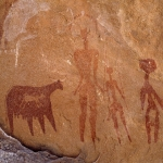 Ennedi Plateau. Faded bichrome cow with white udder facing right. Two faded men facing forwards. Tall man has headdress and holds spear. Short man has round head with three plumes, back-skirt, and holds spear. Third man painted in maroon has burden on head and holds club. Bichrome red cow with udder and white horns. Small antelope facing right superimposed on red cow. Image ID: chaenp0040008