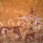 Ennedi plateau. 'Flying' camel with mounted warrior, row of warriors holding spears and shields, bichrome cow with collar and bichrome cattle. Image ID: chaenp0050026