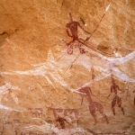 Ennedi plateau. Flying white camel mounted by armed warrior. Image ID: chaenp0050035