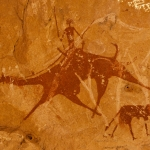 Ennedi plateau. Painting of a camel and a rider, two cows to the left and right. Image ID: chaenp0060036