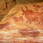 Tassili du Kozen. Large decorated bichrome red and white bull facing left among smaller decorated bulls. Clothed man facing left holding stick and shield with a headdress. Silhouette white cow facing left, bichrome red and white cow facing left, four outline cows facing left. Image ID: chatdk0010004