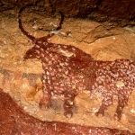 Tassili du Kozen. Detail showing red bull with lines of white spots and cloven hooves superimposing cattle facing left. Image ID: chatdk0010008