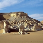 Wadi el Obeyied. Limestone outcrops and cliff. Entrance to cave site just visible at top oif sand dune close to shadow. Image ID: egyweo0010002