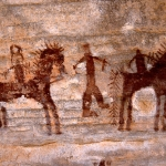 Tagant, Mauritania. Two dark maroon men, one wearing headdress, riding horses with fancy manes and tails separated by man on foot. Image ID: mauaio0010001