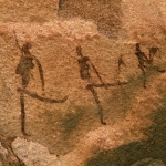 Painted figures with their legs up-perhaps dancing. Some of the only painted art in an area full of engravings (Twyfelfontein)