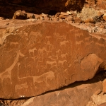 "Panel with carols animal rock engravings in particular a lion facing right with ""pug marks"" (lion footprints at the end of each leg and one oat the end of his tail. Image ID: namdmt0010016"