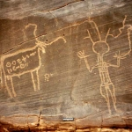 Western Air Mountains, Niger. Pecked outline domestic bull with body decorated with two horizontal lines of ancient Tifinagh script. To right of bull, slim Libyan warrior with round outline head and three feathers, long neck and one earring, striped jacket and breeches, raised hands one holding elongated leg of schematic ostrich. Image ID: nigwam0050024