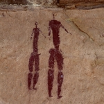 Drakensberg, South Africa. Two men, naked except for beaded arm and bicep bands, stand in twisted perspective looking right. Both men have blank faces and erect penises. Taller man's penis is infibulated. Both men have ring of beads on hips. Image ID: soadrb0080037