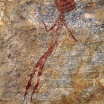 Slender red figure with solid almost-round head, one arm extended and other bent up at elbow, faces forward. Image ID: tankon0030072